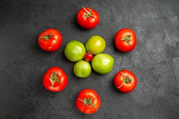 Vista superior de tomates vermelhos e verdes ao redor de um tomate cereja em um solo escuro com espaço de cópia