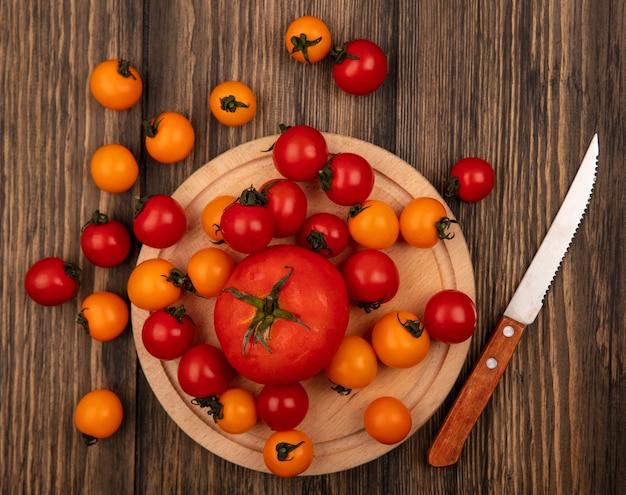 Vista superior de tomates vermelhos em uma placa de cozinha de madeira com uma faca com tomate cereja isolado em uma superfície de madeira
