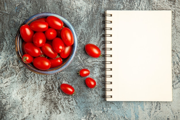 Vista superior de tomates vermelhos frescos com bloco de notas na mesa com luz escura, foto de frutas salada escura