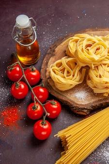 Vista superior de tomates vermelhos frescos com massa crua em uma refeição de macarrão de salada crua de superfície escura