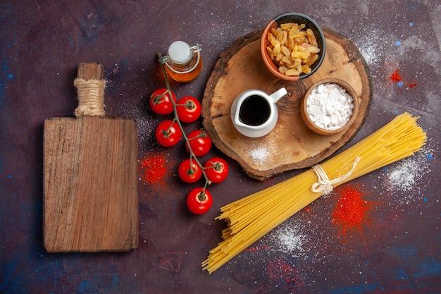 Vista superior de tomates vermelhos frescos com passas e massa crua em fundo escuro salada de refeição