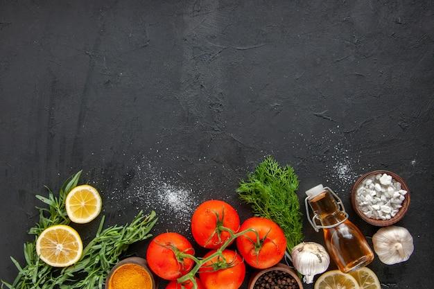 Vista superior de tomates vermelhos frescos com rodelas de limão e alho na mesa escura