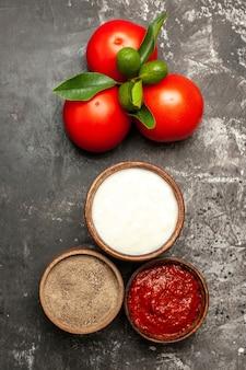 Vista superior de tomates vermelhos frescos com temperos em vegetais vermelhos maduros de superfície escura