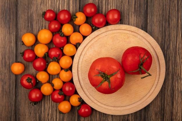 Vista superior de tomates vermelhos frescos em uma placa de cozinha de madeira com tomate cereja isolado em uma parede de madeira