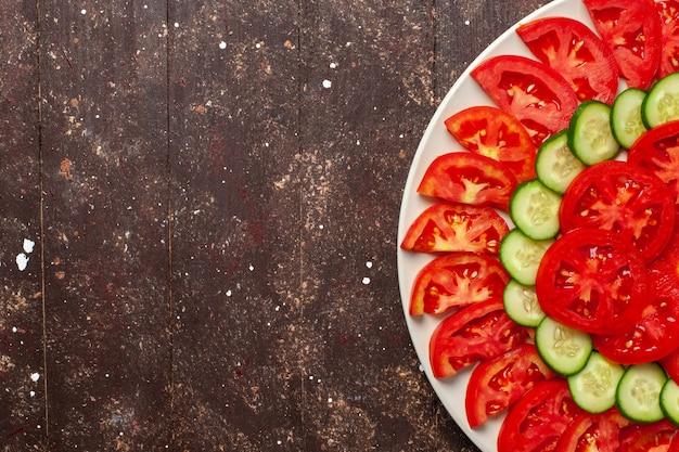 Vista superior de tomates vermelhos frescos fatiados com salada fresca de pepino na mesa marrom