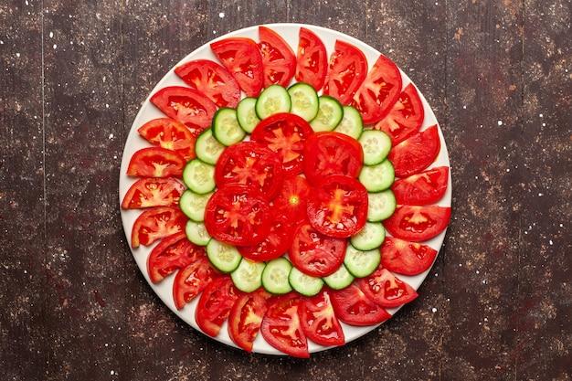 Vista superior de tomates vermelhos frescos fatiados com salada fresca de pepino no espaço marrom