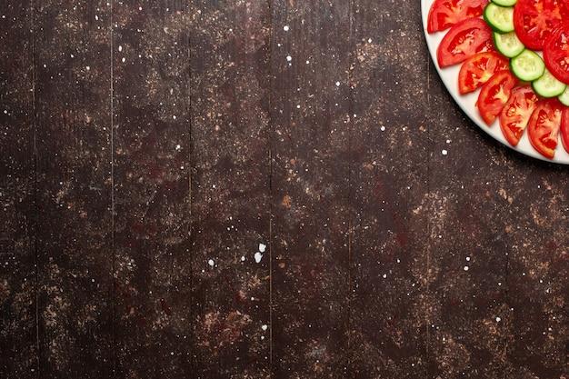 Vista superior de tomates vermelhos frescos fatiados em fatias de salada fresca em espaço marrom