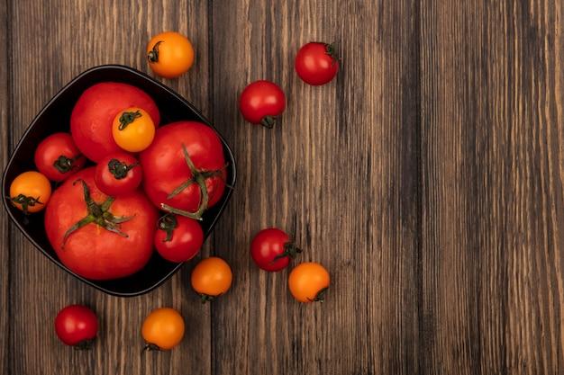 Vista superior de tomates vermelhos grandes em uma tigela com tomates cereja isolados em uma parede de madeira com espaço de cópia