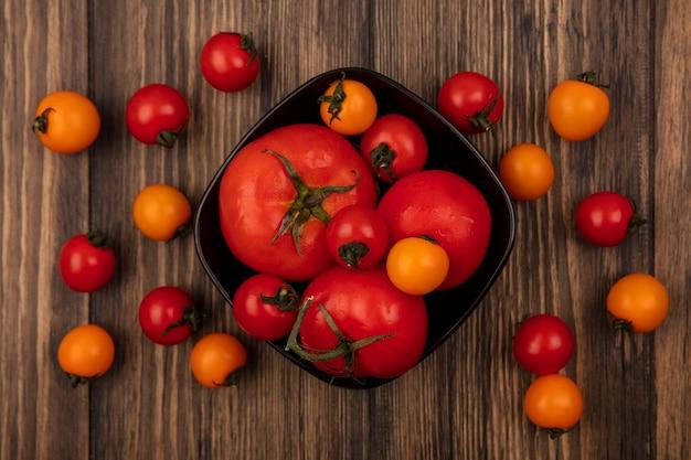 Vista superior de tomates vermelhos macios e grandes em uma tigela com tomates cereja isolados em uma parede de madeira