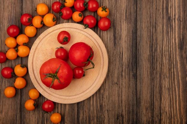 Vista superior de tomates vermelhos saudáveis em uma placa de cozinha de madeira com tomates cereja isolados em um fundo de madeira com espaço de cópia