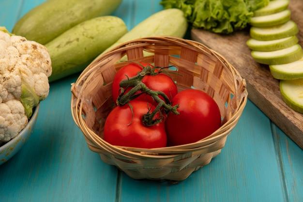 Vista superior de tomates vermelhos suaves em um balde com abobrinhas picadas em uma placa de cozinha de madeira com alface em uma superfície de madeira azul