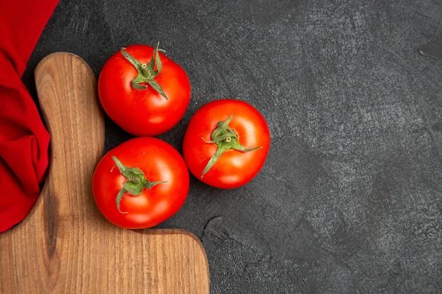 Vista superior de tomates vermelhos, toalha vermelha e uma tábua de cortar em solo escuro com espaço de cópia