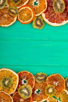 Vista superior de toranja seca e fatias de laranja com kiwi seco sobre fundo verde de madeira, com espaço de cópia