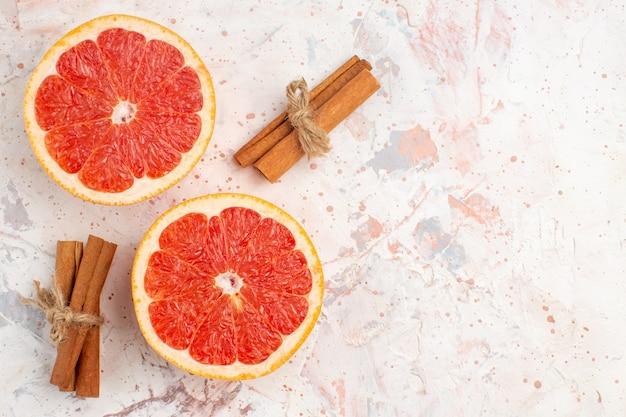 Vista superior de toranjas cortadas em bastões de canela no espaço de cópia da superfície nua