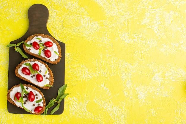 Vista superior de torradas de pão com creme de leite e dogwoods na superfície amarela