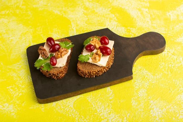 Vista superior de torradas de pão com nozes e queijo na superfície amarela
