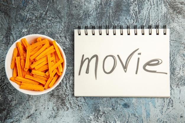 Vista superior de tostas de queijo com bloco de notas escrito em filme sobre superfície clara