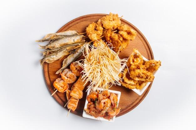 Vista superior de travessa isolada de cerveja de frutos do mar fritos com peixes e camarões
