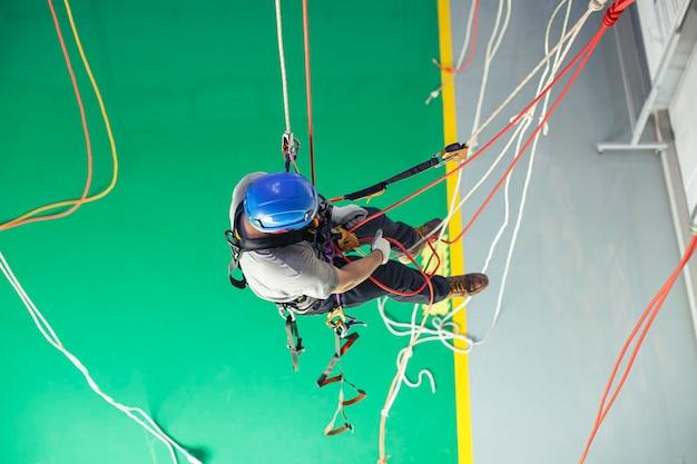 Vista superior de treinamento de trabalhador masculino amarre o acesso por corda em trabalho no alto