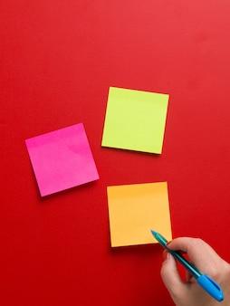 Vista superior de três adesivos de lembrete colorido e uma mão feminina segurando uma caneta azul em um fundo vermelho