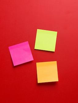 Vista superior de três adesivos de lembrete colorido em um fundo vermelho