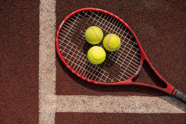Vista superior de três bolas de tênis na raquete por linha branca do playground de esportes
