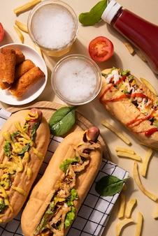 Vista superior de três cachorros-quentes com batatas fritas e bebidas