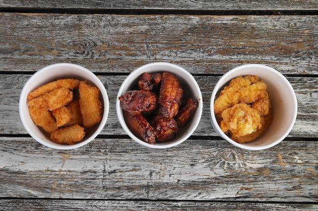 Vista superior de três contêiners de papelão com asas de frango frito na mesa de madeira