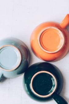 Vista superior de três copos coloridos sobre fundo cinza. tema minimalista abstrato