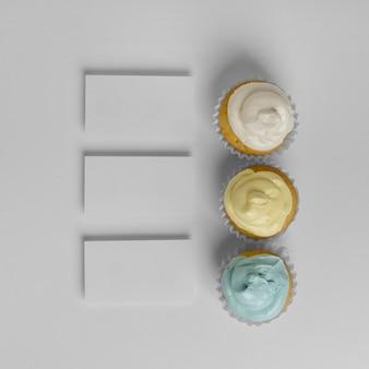 Vista superior de três cupcakes com embalagem e espaço de cópia