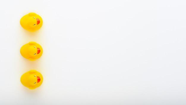 Vista superior de três patinhos amarelos de brinquedo em fundo branco com espaço de cópia