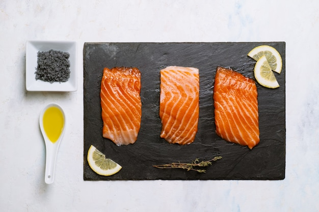 Vista superior de três pedaços de salmão cru em uma placa de ardósia e rodelas de limão com azeite e sal preto