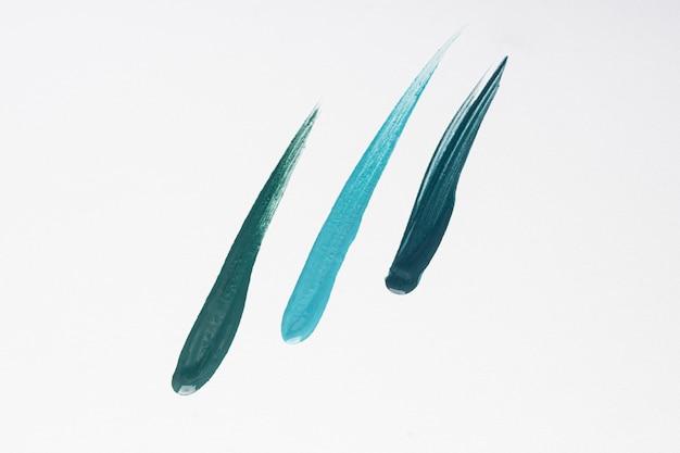 Vista superior de três pinceladas criativas de tinta azul na superfície