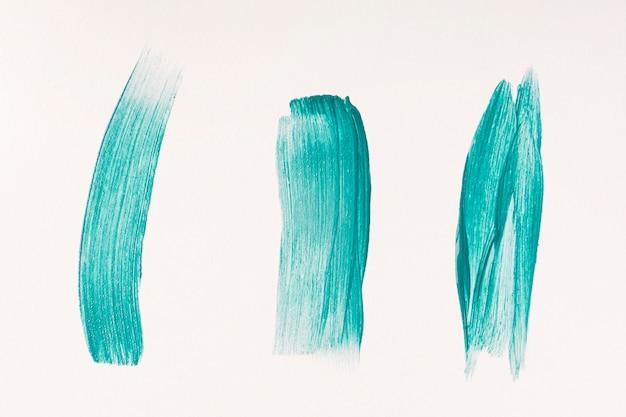 Vista superior de três pinceladas de tinta azul