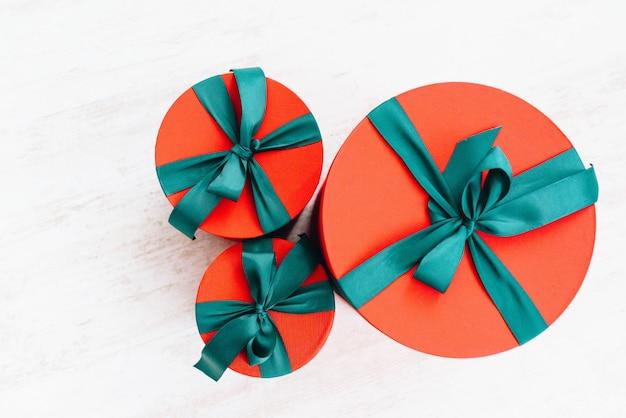 Vista superior de três presentes de natal maravilhosamente embrulhados em grandes caixas redondas
