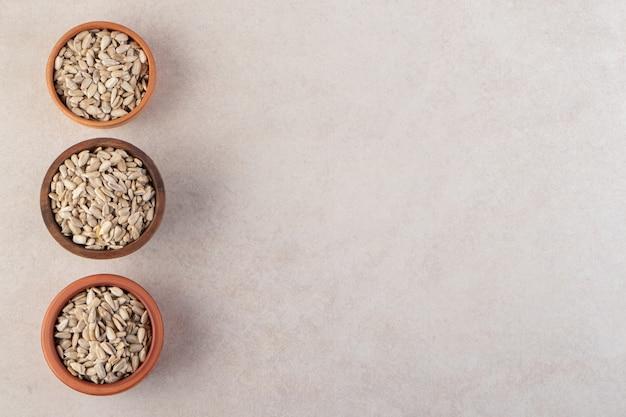 Vista superior de três tigelas cheias com sementes de girassol sem casca