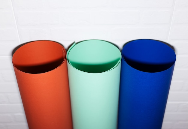 Vista superior de três tubos de papel, lava exuberante, água menta e azul fantasma de cor, na parede de tijolo branco.