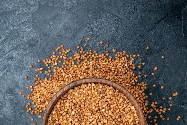 Vista superior de trigo sarraceno cru dentro de um prato marrom na mesa cinza