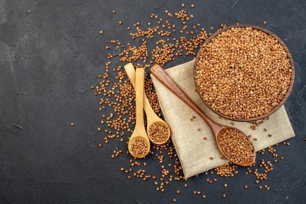 Vista superior de trigo sarraceno marrom dentro do prato com um par de colheres em fundo escuro