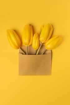 Vista superior de tulipas amarelas em envelope em fundo amarelo. dia dos namorados, dia das mães ou primavera