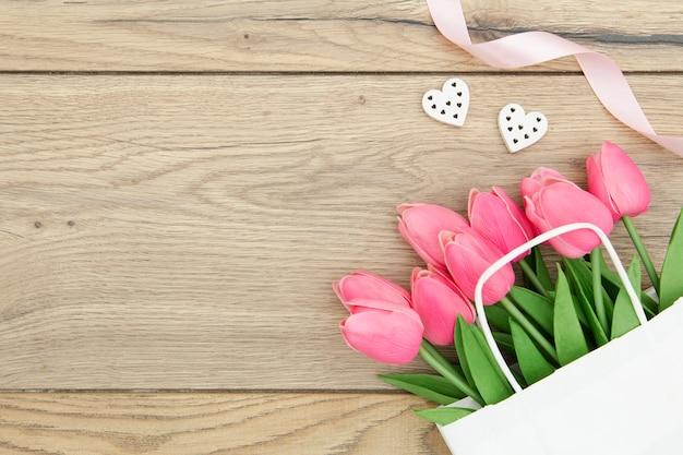 Vista superior de tulipas cor de rosa na mesa de madeira
