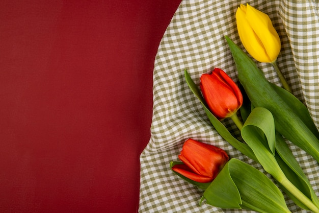 Vista superior de tulipas de cores vermelhas e amarelas em tecido xadrez na mesa vermelha com espaço de cópia