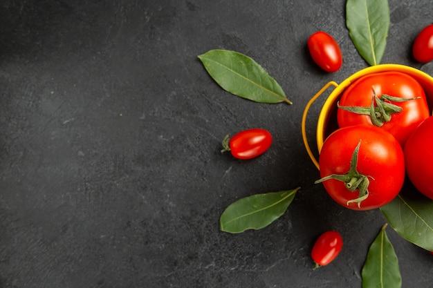 Vista superior de um balde com tomates ao redor de tomates cereja e folhas de louro à direita de um solo escuro
