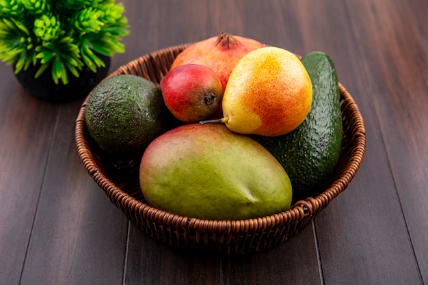 Vista superior de um balde de frutas frescas, como pêra, romã e manga na madeira