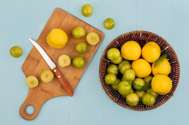 Vista superior de um balde de pêssegos amarelos com fatias de ameixa cereja verde em uma placa de cozinha de madeira com uma faca no fundo azul