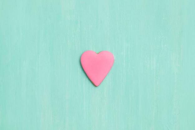 Vista superior de um biscoito de gengibre rosa em forma de coração em fundo turquesa