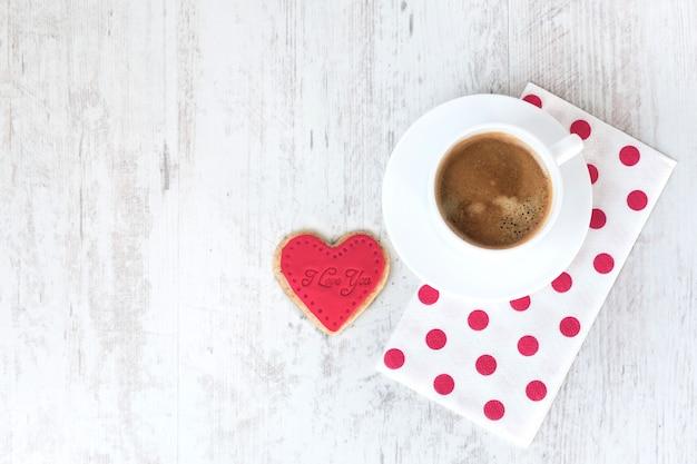 Vista superior de um biscoito em forma de coração e uma xícara de café.
