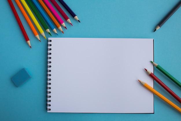 Vista superior de um bloco de notas aberto e lápis de cor na superfície azul. copie o espaço.
