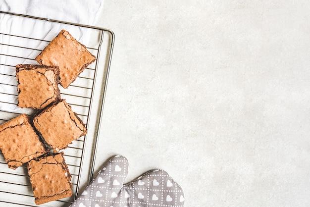 Vista superior de um bolo de brownie caseiro recém-assado cortado em quadrados sobre uma prateleira de apoio. copie o espaço.