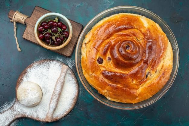 Vista superior de um bolo de cereja assado com cerejas dentro, junto com massa de farinha e cerejas ácidas frescas na mesa escura, bolo de frutas assado chá doce